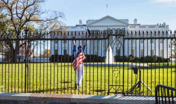Hombre salta la cerca de la Casa Blanca cubierto con una bandera